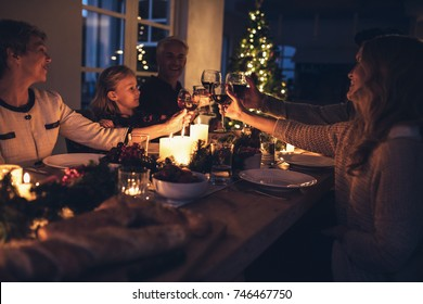 Happy extended family toasting drinks during christmas dinner at home in the living room. Family celebrating Christmas together.