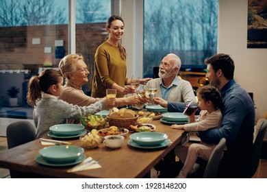 Happy extended family toasting while having lunch together in dining room. - Shutterstock ID 1928148200