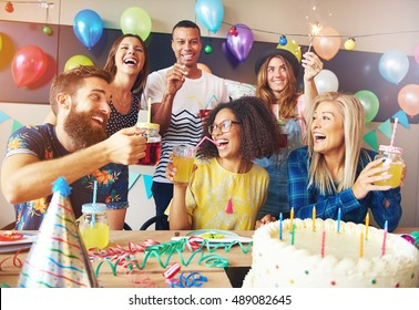 Happy exuberant group of friends celebrating a birthday party toasting the birthday girl laughing and joking
