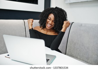 Happy and exults winner fashionable young beautiful african american business woman with afro hairstyle wear in elegant black, sitting and working at laptop.
