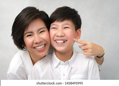 A happy face of asian smart looking preteen boy and mom laughing together. Deciduous teeth, Milk teeth, Healthy and strong, Dental oral care, Bonding, Mother and son, Studio portrait white background.