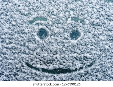 A happy face drawn on a snowy windshield.