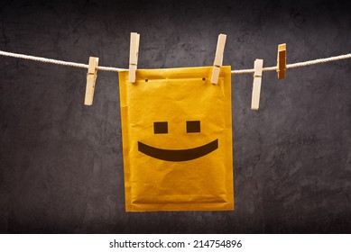 Happy face emoticon on Postal mail Envelope hanging on rope attached with clothes pins. Good news concept.