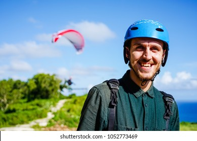 The happy face of the paraglider is close up. Paragliding over the ocean on the island of Bali. The blue sky shimmers with the blue ocean. Close-up view with copy space