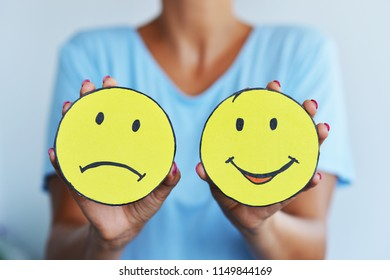 Happy face and sad face, two symbols of emotions or feelings in woman hands suggesting the state o mind