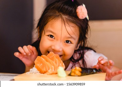 Happy face with salmon sashimi with rice.Little asian girl hungry and ready to eat fresh salmon sashimi in Japanese restuarant. Japanese food. Happy meal and Delicious asian food concept.