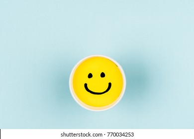 Happy face or smile yellow face on blue textured background with empty space