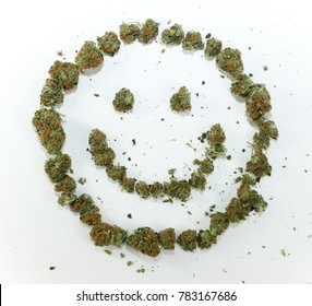 A happy face symbol made with real marijuana on white.