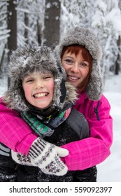 happy faces of mother and son in the winter forest closeup