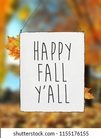 Happy fall you all autumn text on white plate board banner leaves blur background