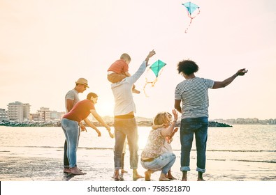 Happy familes flying with kite and having fun on the beach - Parents playing with children outdoor - Travel,love and holidays concept - Main focus on right woman - Warm filter