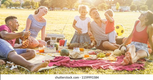 Happy families doing picnic in city park - Young parents having fun with their children in summer time eating, drinking and laughing together - Love and chlidood concept - Main focus on left man face