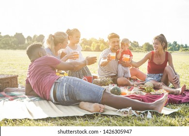 Happy families doing picnic in city park - Young parents having fun with their children in summer time eating, drinking and laughing together - Love and chlidood concept - Focus on people faces