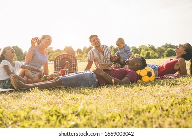 Happy families doing picnic in city park - Young parents having fun with their children in summer time eating and laughing together - Love and chlidood concept - Main focus on left woman face