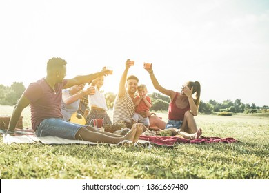 Happy families doing picnic in natur park - Young parents having fun with their children in summer time eating, drinking and laughing together - Love and chlidood concept - Main focus on left man face