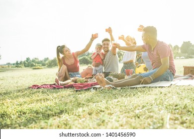 Happy families doing picnic in nature park - Young parents having fun with their children in summer time eating, drinking and laughing together - Love and chlidood concept - Focus on people faces
