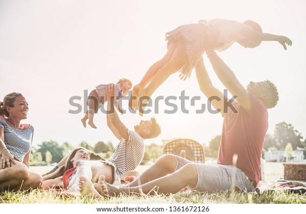 Happy families doing picnic in nature park outdoor - Young parents having fun with children in summer time laughing together - Weekend day concept - Main focus on right man face and daughter