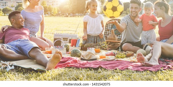 Happy families making picnic in city park - Young parents having fun with their children in summer time eating, laughing and playing together - Love and chlidood concept - Main focus on people faces