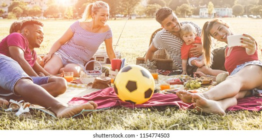 Happy families taking selfie and laughing together at picnic in city park outdoor - Parents friends having fun with children on weekend day - Summer, technology trend and love concept - Focus on faces
