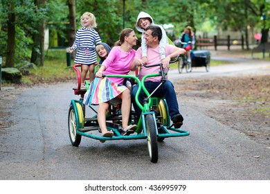 Happy family of 5 riding ricksha bike in vacation park. Father, mother and kids enjoying time together outdoors during summer holidays.