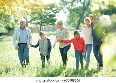 Happy family of 6 walking in park