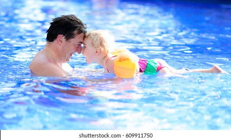 Happy family, active father with little child, adorable toddler girl, having fun together in outdoors swimming pool in water park during sunny summer sea vacation in tropical resort