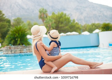 Happy family, active mather with little child, adorable toddler girl, having fun together in outdoors swimming pool
