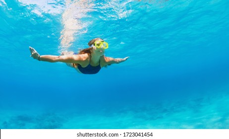 Happy family - active young woman in snorkeling mask dive, swim underwater to see tropical fishes in sea lagoon pool. Travel adventure, swimming activity, watersports on summer beach cruise with kid