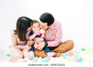 Happy Family - Adorable Asian Chubby Baby Boy Playing a Colorful Plastic Ball with Father and Mother in White Living Room on Vacation , Lifestyle Concept