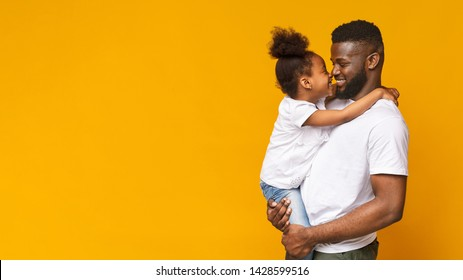 Happy family. Adorable little african girl touching noses with her daddy, orange panorama background with empty space