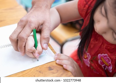 Happy family. Adult man helping the child girl drawing. Dad and child daughter together draws are engaged in creativity in kindergarten.