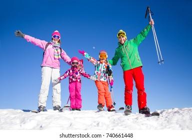 happy family in alpine ski equipment  at the ski resort