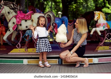 Happy family in the amusement park. Mother gives her daughter candyfloss.