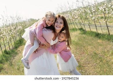 Fröhliche Familie im Apfelgarten. Mama und zwei Zwillingstöchter haben Spaß und Umarmung.