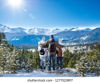 Happy family with arms around each other enjoying beautiful  mountain view on winter  hiking trip. Rocky Mountain National Park. Close to Estes Park, Colorado, USA