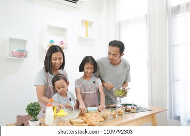 Happy family asian cooks in the kitchen at home