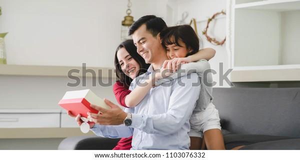 アジアの幸せな家族のグループのポートレート、家族の日または父の日、母の日、サプライズギフト。父親を抱き締めるポートレート娘、リビングルームでの明るい関係が幸せ。