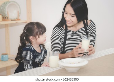 Happy family of asian mom is drinking milk with her cute daughter in the morning. Photo series of family, kids and happy people concept.