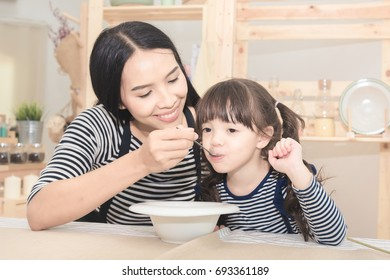 Happy family of asian mom feeding healthy breakfast to her cute daughter in the morning. Photo series of family, kids and happy people concept.