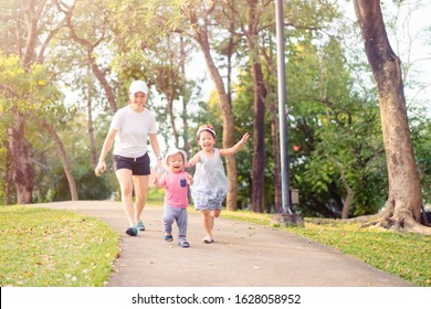 Happy family asian mother and children running in summer nature park in the morning.Family exercising and jogging together at the park.Green ecology, Fresh air, City Lifestyle and Asian Single mom.