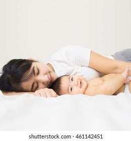 happy family. asian mother playing with her baby in the bedroom.