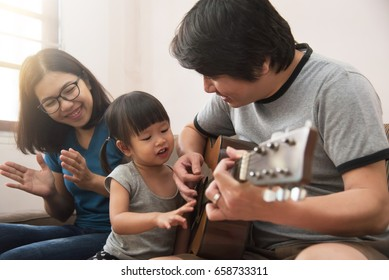 Happy family. Asian young father, mother and daughter playing the guitar together.