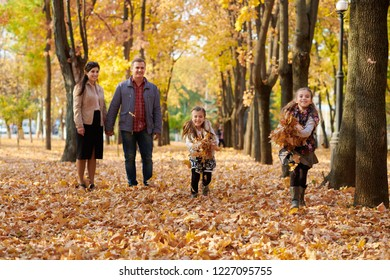 Happy family is in autumn city park. Children and parents running with leaves.. They posing, smiling, playing and having fun. Bright yellow trees.