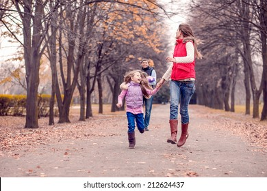 Happy family in autumn park. Autumn walk, November