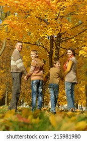 Happy family in autumn park,back view
