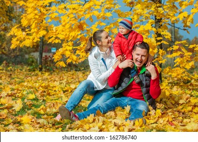 Happy family with baby boy at beautiful autumn park