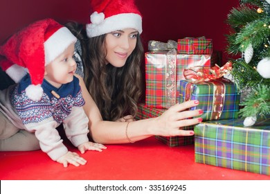 Happy family of baby and mother near the Christmas tree with many gift and present box! Mom and kid dressed in red Santa hat. Xmas and New Year holiday!