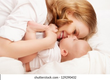 happy family. baby and mother play, kiss, tickle, laugh in white bed
