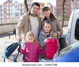 Happy family with baggage at parking lot in spring day