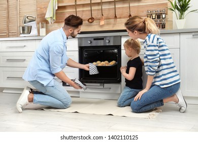 Happy family baking cookies in oven at home